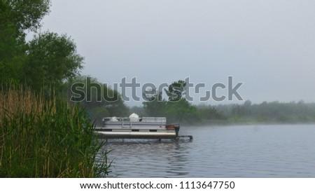 Pontoon boat on lift on foggy Lake Irving in Bemidji Minnesota #1113647750