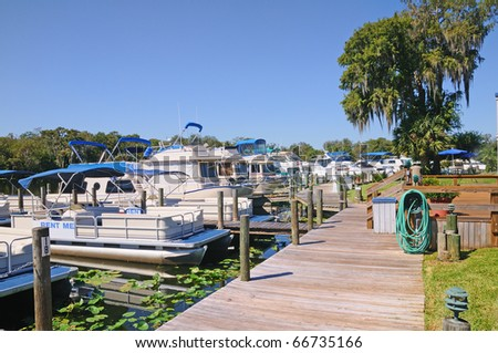 Pontoon boats and houseboats tied up at the marina,s dock in Deland, Florida.