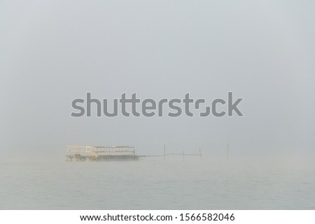 Pontoon floated in the river, steel raft floats in the middle of the lake and is covered with fog #1566582046