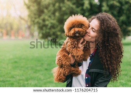 Poodle dog and his owner. Adorable puppy and young woman having fun in park, copy space