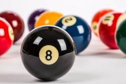 Pool balls in random order with Eight Ball in foreground on plain white backdrop.