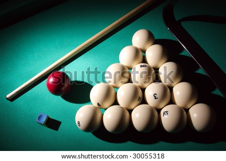 Pool balls on light beam. Balls pyramid with cue on a pool table.