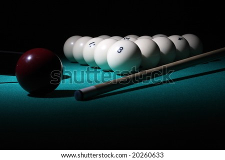 "Pool balls on light beam. Balls pyramid with number 8 ball on a foreground. ""Low-key"" scene."