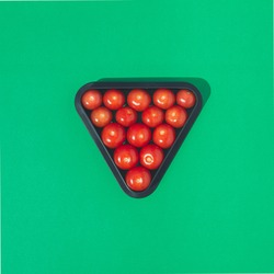 Pool Billiard rack with red cherry tomatoes on a vibrant green background.  Minimal flat lay