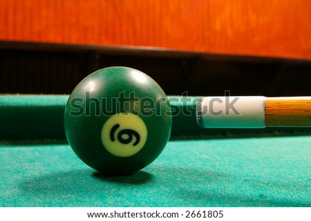 Pool cue and ball shot from low angle