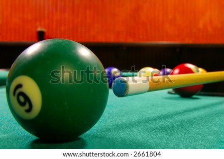 Pool cue and balls shot from low angle, cue tip is sharp
