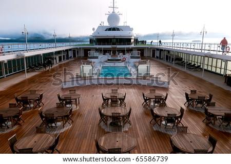 pool deck scene onboard luxury cruise liner traveling alaska's inside passage at dawn