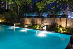 Pool lighting in backyard at night for family lifestyle and living area.  Luxury design with good light and clean landscaping.