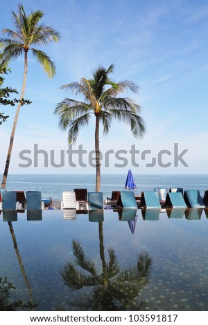 Pool on a beach of the Thai gulf. The palm tree and beach armchairs are reflected in a smooth water surface