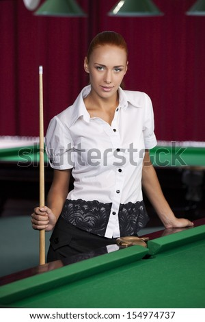 Pool player. Confident young woman holding pool cue and smiling