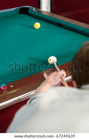Pool player lining up a shot on the nine ball, with selective focus on hand, cue and cue ball