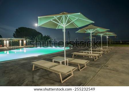 Pool, sunbeds and umbrellas at night. Night lights. Greece, Gythio #255232549