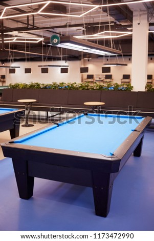 Pool table with blue cloth in billiard club.