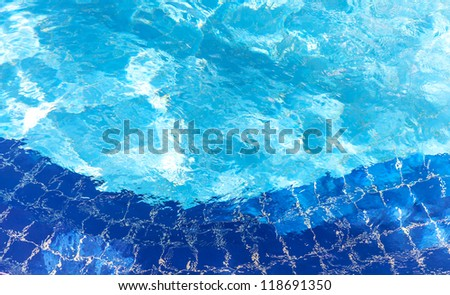Pool water ripple background texture with bright reflections and blue tiles.
