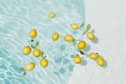 Pool Water With Lemons. Pure Aqua Surface With Glares Pattern And Floating Fresh Citrus. Clear Liquid With Sunlight Reflection In Summer.