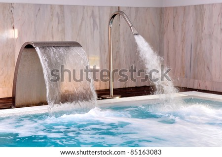 Pool with streams of water in modern spa
