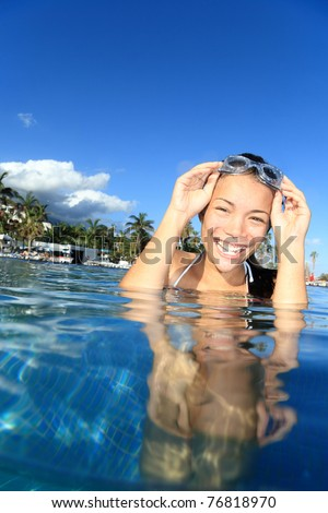 Pool woman on holidays in tropical resort swimming. Beautiful girl smiling with goggles. Asian Caucasian young woman model. - stock photo