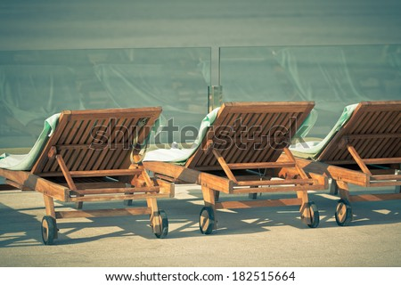 Poolside Chairs with Sea view. Horizontal vintage style shot