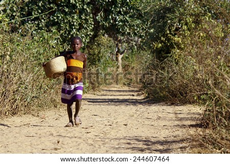 Poor african girl walking the sandy path with basket in hand