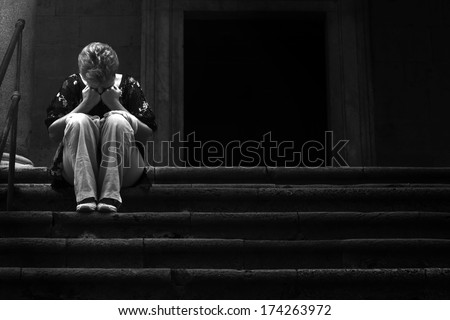 Poor and afflicted woman with hands on face sitting on the steps of a church