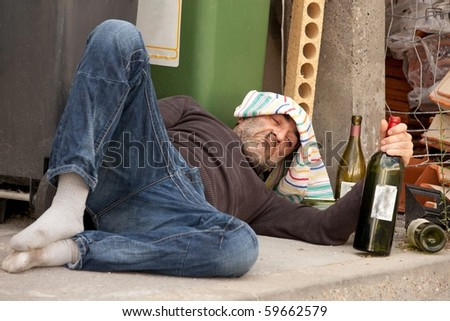 poor and drunk man lying on sidewalk  with bottles of wine near trash can