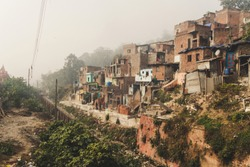 Poor area of Haridwar, India. House poor people on the hillside in front of a dirty river. social problems of our time.