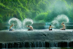 Poor Asian Children were having fun by playing water in an artificial dam with beautifull forest backgroud