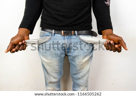 Poor Black man in jeans with empty pocket. Nigerian African American Man showing empty denim pockets on white background for jobless, broke, bankruptcy, bad credit, debt and financial trouble Concept.