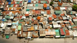 Poor district and slums with shacks in a densely populated area of Manila aerial view.