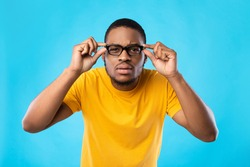 Poor Eyesight Problem. Black Guy In Glasses Squinting Eyes Looking At Camera Posing In Studio Over Blue Background. Vision Health Issue Concept. Portrait Of Nearsighted Man Wearing Eyeglasses