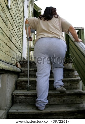Poor fat disabled woman entering her shabby old house.