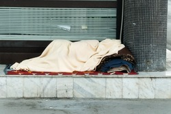 Poor homeless or refugee person covered with a blanket sleep in the shadow on the street