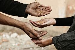 Poor homeless people sharing food outdoors, closeup