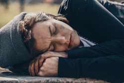 Poor homeless woman lying on bench outdoors
