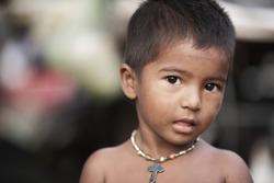 Poor Indian child in outdoor background.