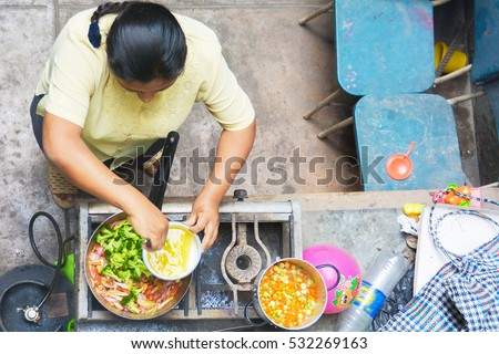 Poor latin woman cooking - view above