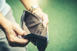 Poor man bankrupt with no credit in debt hand hold empty black leather wallet because economy down turn depression crisis fail working saving finance money plan loss job unemploy. No money to pay