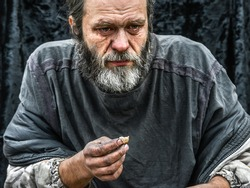 poor man homeless with dirty hands eating piece of bread in modern capitalism society. Economic recession, unemployment, poverty, hunger, retirement, global crisis, inequality problem concept.