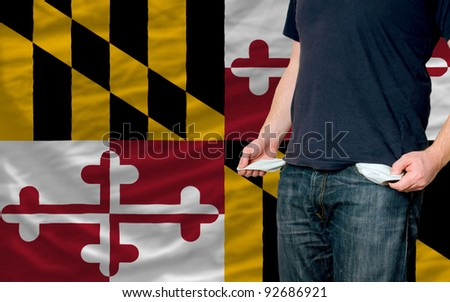 poor man showing empty pockets in front of american state of maryland flag