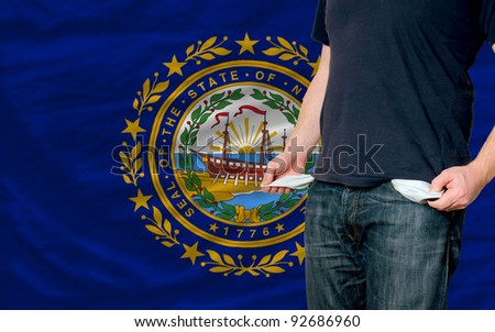 poor man showing empty pockets in front of american state of new hampshire flag - stock photo