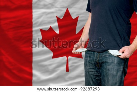 poor man showing empty pockets in front of canada flag
