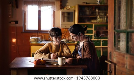 Poor mature mother and small daughter learning indoors at home, poverty concept. Foto stock ©
