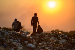 Poor people collect garbage for sale People living in garbage heaps walking to collect recyclable waste to be sold to poverty concept world environment day