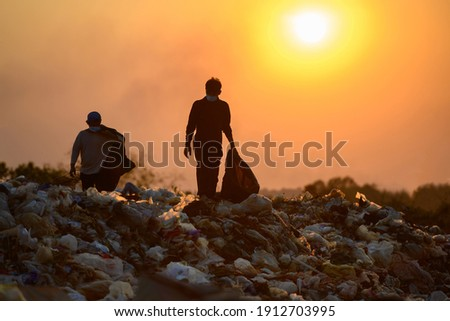 Poor people collect garbage for sale People living in garbage heaps walking to collect recyclable waste to be sold to poverty concept world environment day Stockfoto ©