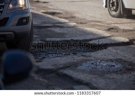 poor quality road surface in the city, asphalt on the roadway is broken without repair, a lot of holes that have to go around cars, the danger of an accident, the consequences of an earthquake on road