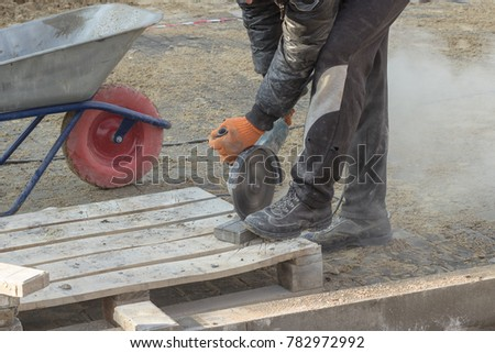 Poor safety. A man is sawing a paving slab with a bulgarian, exposing himself to danger
