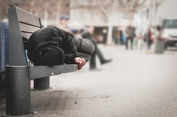Poor tired depressed hungry homeless man or refugee sleeping on the wooden bench on the urban street in the city, social documentary concept