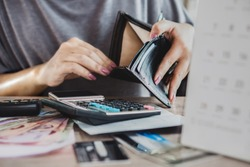 poor woman hand open empty purse looking for money for credit card debt, bankrupt concept