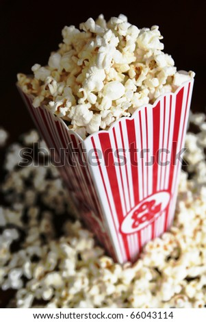 Pop corn container full of pop corn on black background
