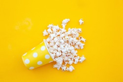 pop corn in a vase in yellow background.top view.Minimalist